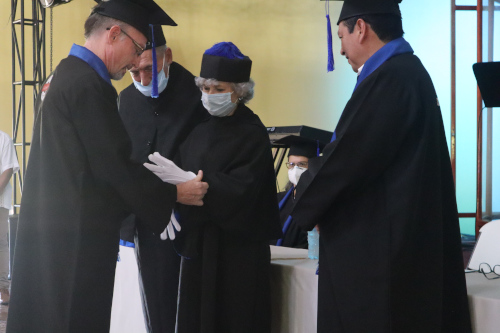 Charles Norton puts gloves on Sue Kershner as she receives Honorary Doctorate in Theology